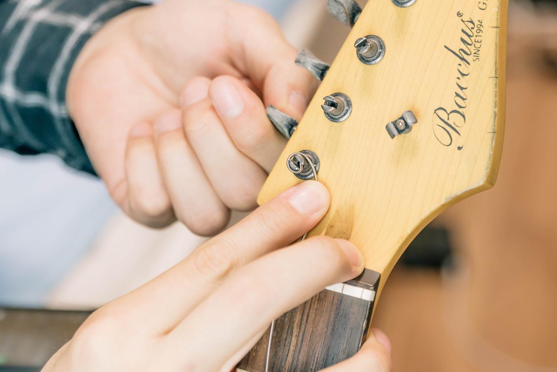 指で押さえながらペグを巻いて弦を巻きつけていく